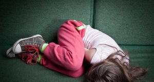 Little Girl Curled Up In Fetal Position